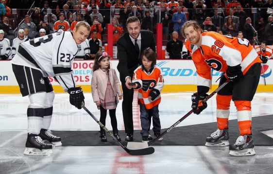 PHILADELPHIA, PA - NOVEMBER 17: Former Philadelphia Flyer and Los Angeles King Simon Gagne, along with his children Lily-Rose and Matthew, join Dustin Brown #23 of the Los Angeles Kings and Claude Giroux #28 of the Philadelphia Flyers for a ceremonial puck drop during a pre-game ceremony honoring his retirement from the NHL on November 17, 2015 at the Wells Fargo Center in Philadelphia, Pennsylvania.  (Photo by Len Redkoles/NHLI via Getty Images)