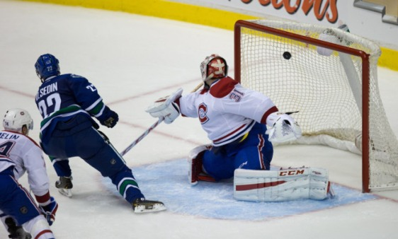 Vancouver Canucks' Daniel Sedin, left, of Sweden, scores the winning goal against Montreal Canadiens goalie Carey Price during overtime NHL hockey action in Vancouver, B.C., on Thursday October 30, 2014. THE CANADIAN PRESS/Darryl Dyck