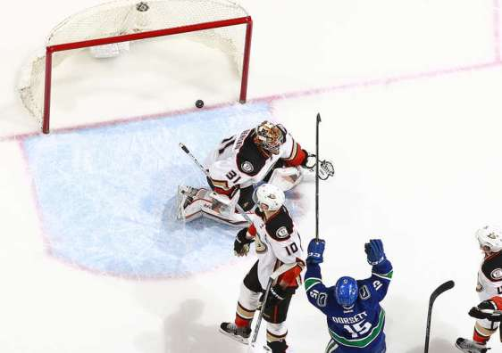 VANCOUVER, BC - JANUARY 1: the puck sits in the net behind Frederik Andersen #31 of the Anaheim Ducks as Derek Dorsett #15 of the Vancouver Canucks celebrates the goal of Christopher Tanev #8 during their NHL game at Rogers Arena January 1, 2016 in Vancouver, British Columbia, Canada. Vancouver won 2-1. (Photo by Jeff Vinnick/NHLI via Getty Images)