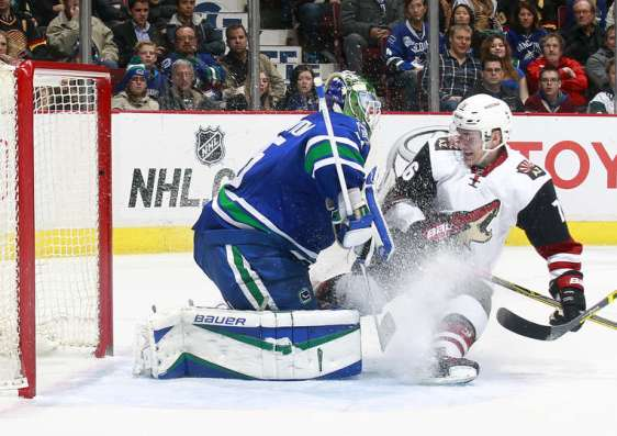 VANCOUVER, BC - JANUARY 4: Jacob Markstrom #25 of the Vancouver Canucks looks on as Laurent Dauphin #76 of the Arizona Coyotes skates in to the net during their NHL game at Rogers Arena January 4, 2016 in Vancouver, British Columbia, Canada. Arizona won 3-2. (Photo by Jeff Vinnick/NHLI via Getty Images)