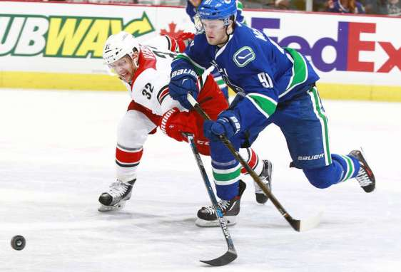 VANCOUVER, BC - JANUARY 6: Kris Versteeg #32 of the Carolina Hurricanes reaches to check Jared McCann #91 of the Vancouver Canucks during their NHL game at Rogers Arena January 6, 2016 in Vancouver, British Columbia, Canada. Vancouver won 3-2. (Photo by Jeff Vinnick/NHLI via Getty Images)