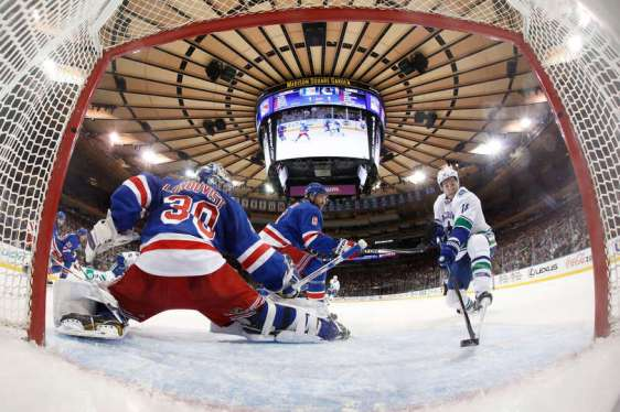 NEW YORK, NY - JANUARY 19: Alex Burrows #14 of the Vancouver Canucks redirects the puck into the net past Henrik Lundqvist #30 of the New York Rangers for a goal in the second period at Madison Square Garden on January 19, 2016 in New York City. (Photo by Jared Silber/NHLI via Getty Images)