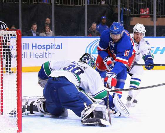 NEW YORK, NY - JANUARY 19: Ryan Miller #30 of the Vancouver Canucks stops Rick Nash #61 of the New York Rangers during the overtime period at Madison Square Garden on January 19, 2016 in New York City. The Rangers defeated the Canucks 3-2 in overtime. (Photo by Bruce Bennett/Getty Images)