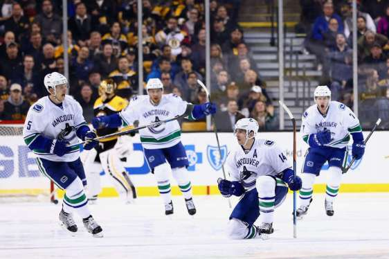 BOSTON, MA - JANUARY 21: Alex Burrows #14 of the Vancouver Canucks, second from right, celebrates wiht Luca Sbisa #5 and Linden Vey #7 after scoring against the Boston Bruins during the third period at TD Garden on January 21, 2016 in Boston, Massachusetts. The Canucks defeat the Bruins 4-2. (Photo by Maddie Meyer/Getty Images)