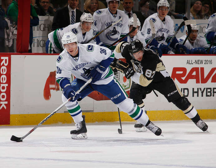 PITTSBURGH, PA - JANUARY 23: Jannik Hansen #36 of the Vancouver Canucks moves the puck up ice in front of Sidney Crosby #87 of the Pittsburgh Penguins at Consol Energy Center on January 23, 2016 in Pittsburgh, Pennsylvania. (Photo by Gregory Shamus/NHLI via Getty Images)
