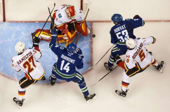 VANCOUVER, BC - OCTOBER 10: Bo Horvat #53 of the Vancouver Canucks shoots the puck past goalie Jonas Hiller #1 of the Calgary Flames while Dougie Hamilton #27 and Mark Giordano #5 of the Calgary Flames battle with Alexandre Burrows #14 in front of the net in NHL action on October, 10, 2015 at Rogers Arena in Vancouver, British Columbia, Canada. (Photo by Rich Lam/Getty Images)