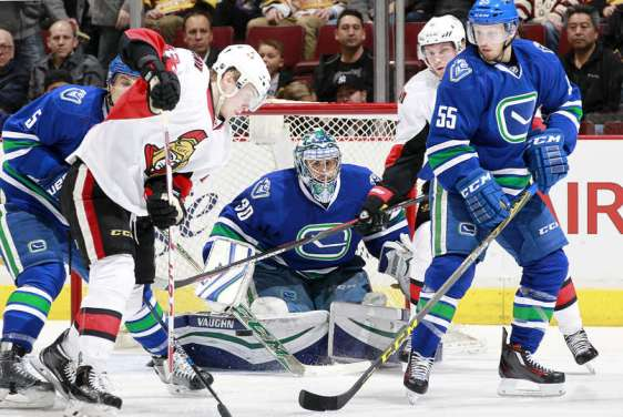 VANCOUVER, BC - FEBRUARY 25: Ryan Miller #30 of the Vancouver Canucks peers through a crowd for the puck during their NHL game against the Ottawa Senators at Rogers Arena February 25, 2016 in Vancouver, British Columbia, Canada. (Photo by Jeff Vinnick/NHLI via Getty Images)