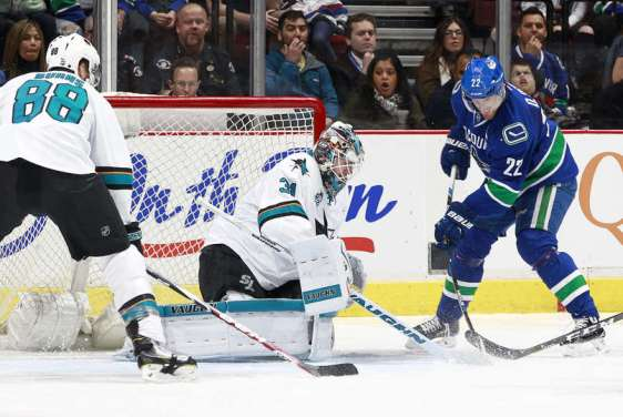 VANCOUVER, BC - FEBRUARY 28: Daniel Sedin #22 of the Vancouver Canucks bats at a loose puck for a goal on Martin Jones #31 of the San Jose Sharks as Brent Burns #88 of the Sharks watches during their NHL game at Rogers Arena February 28, 2016 in Vancouver, British Columbia, Canada. (Photo by Jeff Vinnick/NHLI via Getty Images)