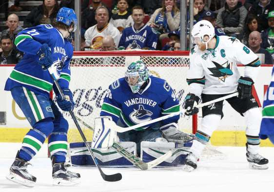 VANCOUVER, BC - FEBRUARY 28: Joe Pavelski #8 of the San Jose Sharks and Ben Hutton #27 of the Vancouver Canucks watch Ryan Miller #30 of the Canucks make a save during their NHL game at Rogers Arena February 28, 2016 in Vancouver, British Columbia, Canada. (Photo by Jeff Vinnick/NHLI via Getty Images)