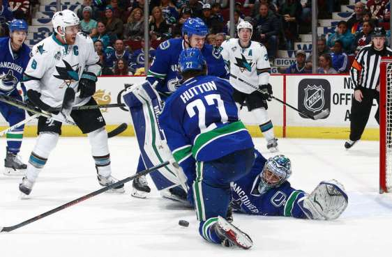 VANCOUVER, BC - FEBRUARY 28: Joe Pavelski #8 of the San Jose Sharks watches as Ryan Miller #30 of the Vancouver Canucks reaches back to make a save in front of Ben Hutton #27 and Derek Dorsett #15 of the Canucks during their NHL game at Rogers Arena February 28, 2016 in Vancouver, British Columbia, Canada. San Jose won 4-1. (Photo by Jeff Vinnick/NHLI via Getty Images)