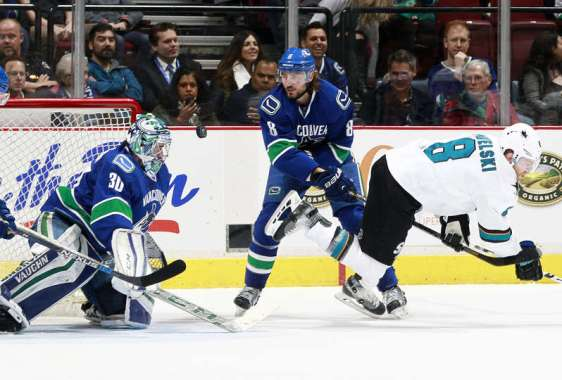 VANCOUVER, BC - FEBRUARY 28: Christopher Tanev #8 of the Vancouver Canucks checks Joe Pavelski #8 of the San Jose Sharks as Ryan Miller #30 of the Canucks eyes the puck during their NHL game at Rogers Arena February 28, 2016 in Vancouver, British Columbia, Canada. (Photo by Jeff Vinnick/NHLI via Getty Images)