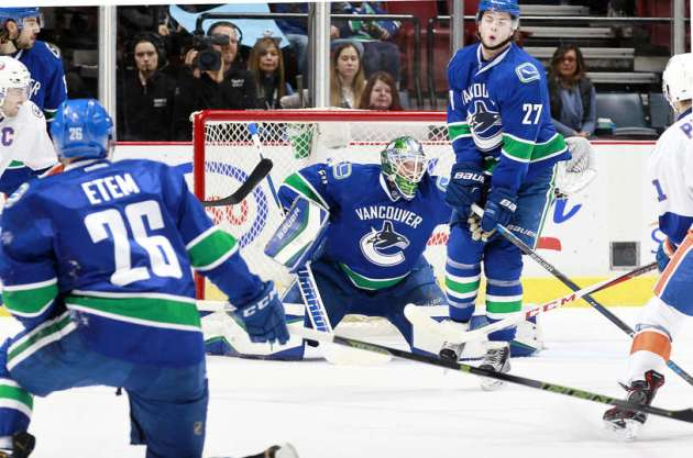 VANCOUVER, BC - MARCH 1: Ben Hutton #27 winces as Emerson Etem #26 and Jacob Markstrom #25 of the Vancouver Canucks follow the puck against the New York Islanders during their NHL game at Rogers Arena March 1, 2016 in Vancouver, British Columbia, Canada. (Photo by Jeff Vinnick/NHLI via Getty Images)