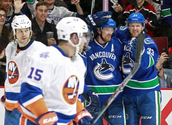 VANCOUVER, BC - MARCH 1: Henrik Sedin #33 congratulates goal scorer Daniel Sedin #22 of the Vancouver Canucks in front of Cal Clutterbuck #15 and Matt Martin #17 of the New York Islanders during their NHL game at Rogers Arena March 1, 2016 in Vancouver, British Columbia, Canada. New York won 3-2. (Photo by Jeff Vinnick/NHLI via Getty Images)