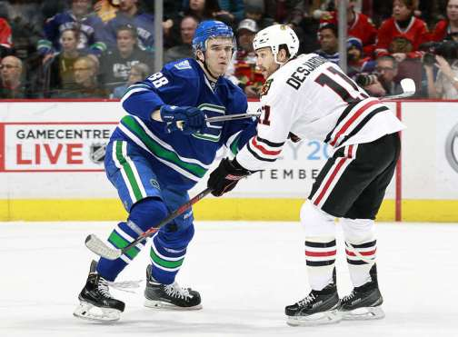 VANCOUVER, BC - MARCH 27: Nikita Tryamkin #88 of the Vancouver Canucks checks Andrew Desjardins #11 of the Chicago Blackhawks during their NHL game at Rogers Arena March 27, 2016 in Vancouver, British Columbia, Canada. (Photo by Jeff Vinnick/NHLI via Getty Images)