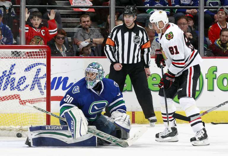 VANCOUVER, BC - MARCH 27: Marian Hossa #81 of the Chicago Blackhawks watches as a shot by Andrew Ladd #16 beats Ryan Miller #30 of the Vancouver Canucks for a goal during their NHL game at Rogers Arena March 27, 2016 in Vancouver, British Columbia, Canada. Chicago won 3-2. (Photo by Jeff Vinnick/NHLI via Getty Images)