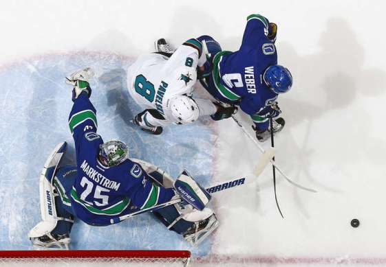 VANCOUVER, BC - MARCH 29: Jacob Markstrom #25 of the Vancouver Canucks makes a save while Joe Pavelski #8 of the San Jose Sharks and Yannick Weber #6 of the Canucks pursue the rebound during their NHL game at Rogers Arena March 29, 2016 in Vancouver, British Columbia, Canada. San Jose won 4-1. (Photo by Jeff Vinnick/NHLI via Getty Images)