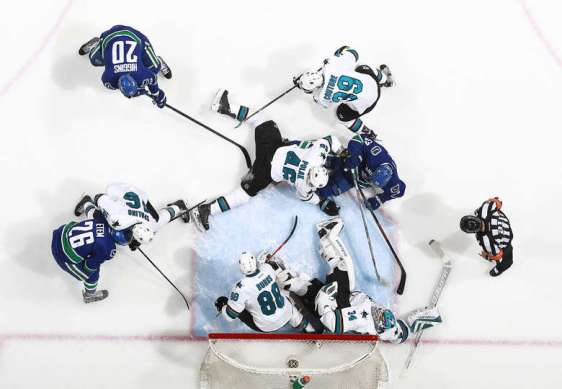 VANCOUVER, BC - MARCH 29: James Reimer of the San Jose Sharks sprawls in a crowd of players to make a save during their NHL game at Rogers Arena March 29, 2016 in Vancouver, British Columbia, Canada. San Jose won 4-1. (Photo by Jeff Vinnick/NHLI via Getty Images)